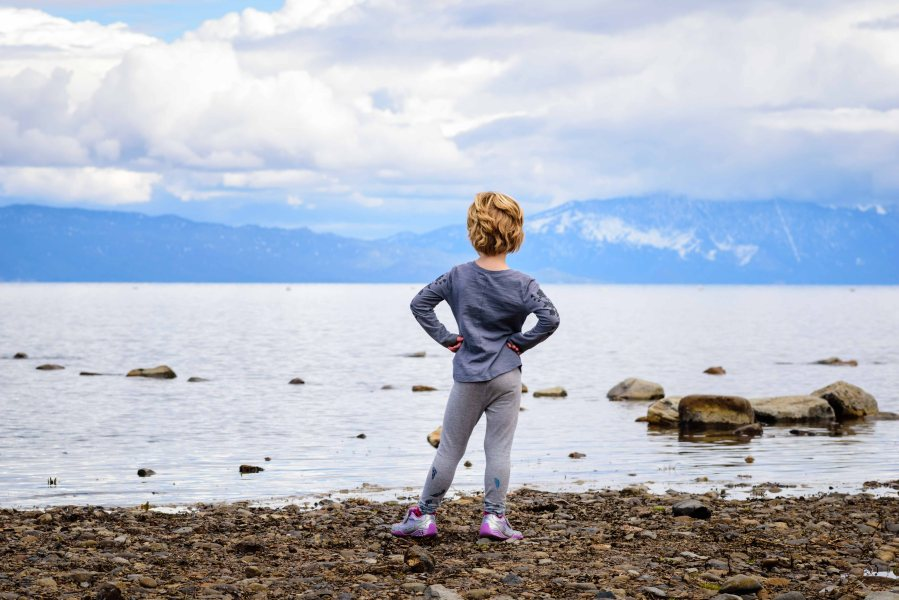 Strong confident girl standing at the edge of lake tahoe